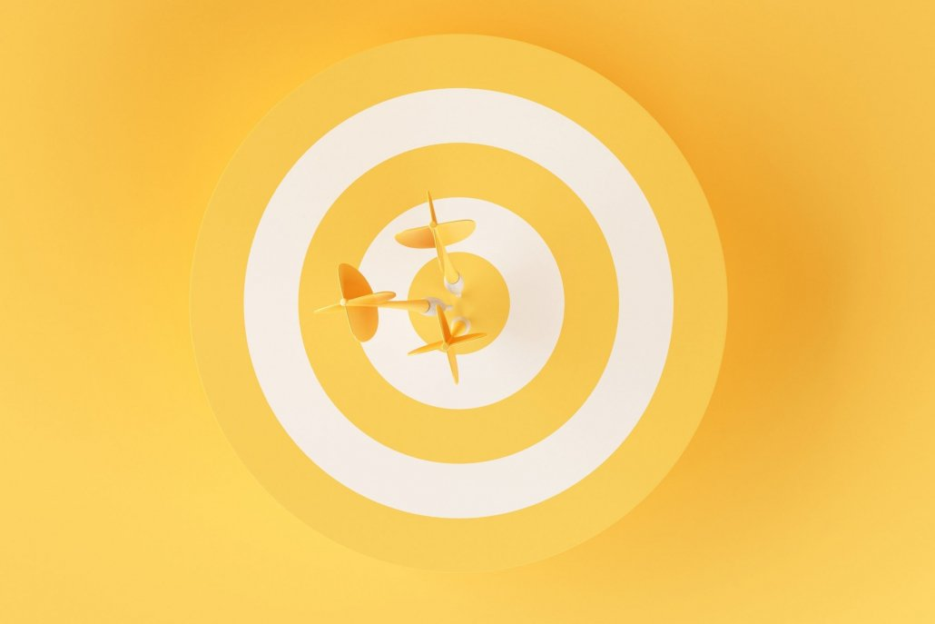 Yellow target with darts in