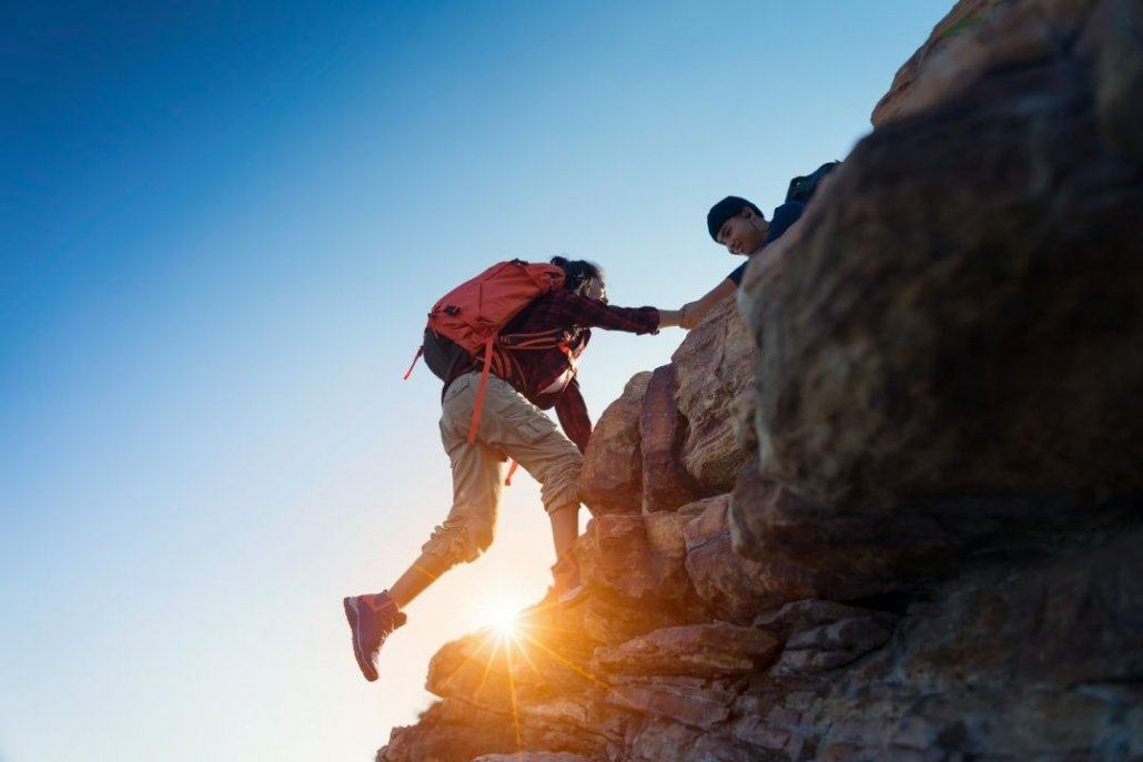 One person helping another person up a rock face